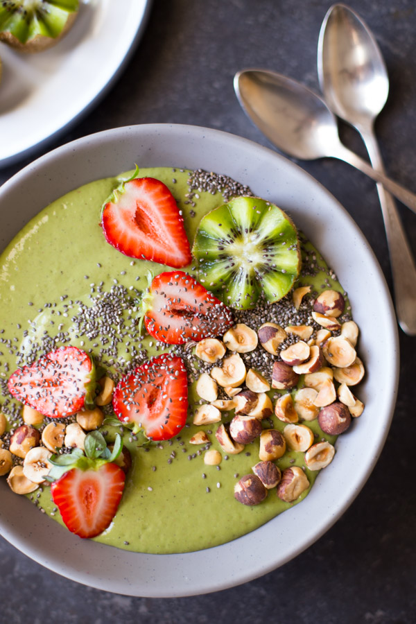 Strawberry Kiwi Protein Smoothie Bowl topped with sliced fresh strawberries and kiwi, hazelnuts, and chia seeds, with two spoons next to the bowl.