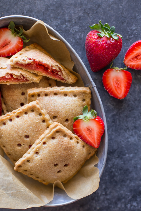 Whole Wheat Strawberry Rhubarb Fruit Pockets in a metal bowl, with some fresh strawberries in the bowl and next to it.