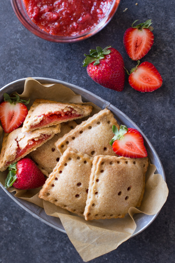 Whole Wheat Strawberry Rhubarb Fruit Pockets in a metal bowl, with some fresh strawberries in the bowl and next to it, along with a bowl of the strawberry rhubarb filling.