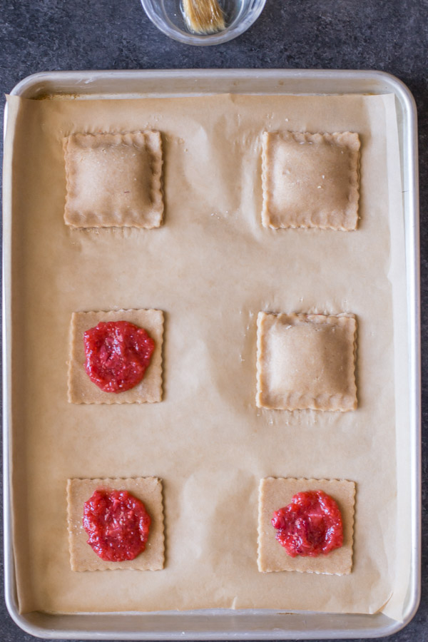 Whole Wheat Strawberry Rhubarb Fruit Pockets being assembled on a parchment paper lined baking sheet.