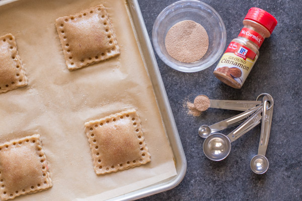 Whole Wheat Strawberry Rhubarb Fruit Pockets on a parchment paper lined baking sheet, with a bowl of cinnamon sugar, a spice container of McCormick Ground Cinnamon and some measuring spoons next to he baking sheet.