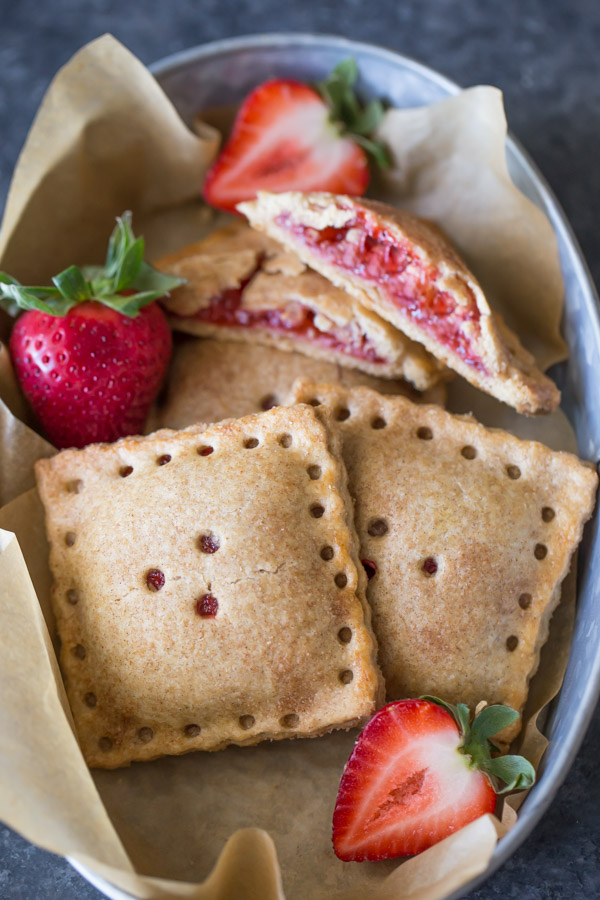 Whole Wheat Strawberry Rhubarb Fruit Pockets in a metal bowl, with some fresh strawberries.