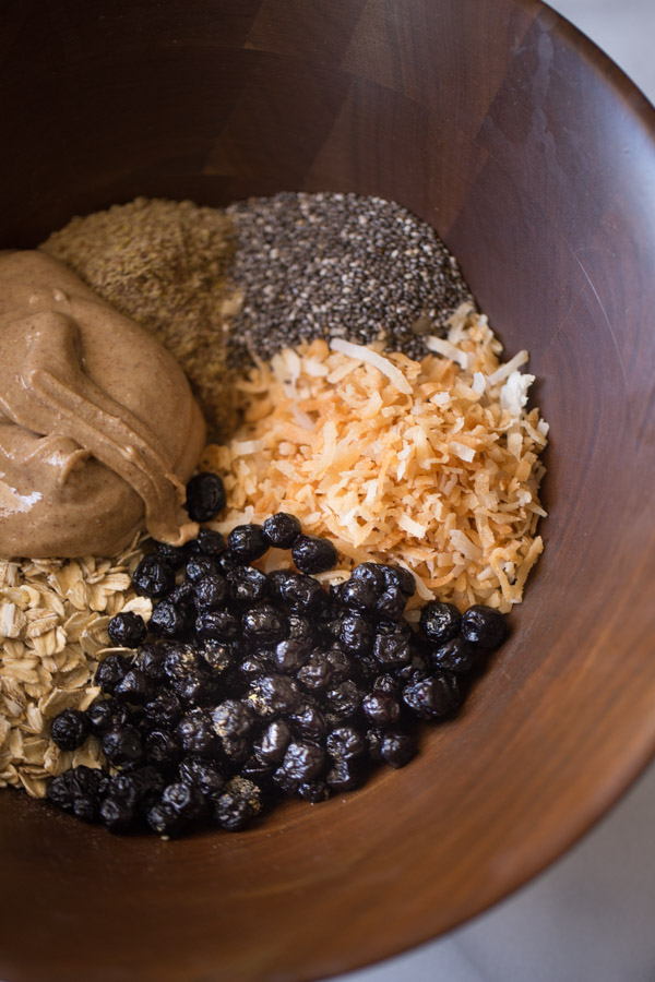 A wood bowl with all the ingredients for the Blueberry Muffin Energy Bites in it.