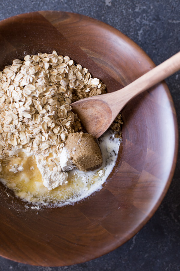A wood bowl of the melted butter, brown sugar, flour, oats, and baking soda, with a wooden spoon in it.