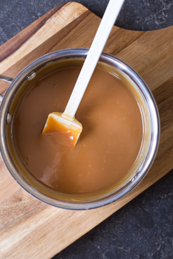 Caramel in a sauce pan with a spatula.