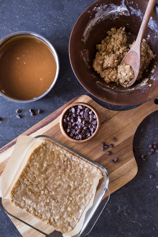 A parchment paper lined baking pan with the bottom layer of the oatmeal mixture in it, sitting on a cutting board with a small bowl of chocolate chips, with the sauce pan of caramel and the bowl of the remaining oatmeal mixture next to the cutting board.