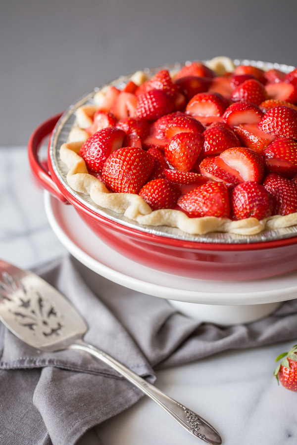 A Fresh Strawberry Pie in a pie plate, sitting on top of a cake stand, with a serving utensil next to it.