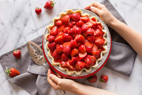 A Fresh Strawberry Pie in a pie plate, sitting on a cloth napkin with a serving utensil and whole strawberries next to it.