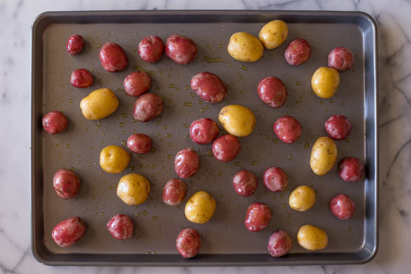 A baking sheet with potatoes coated with olive oil and seasoned with salt and pepper.