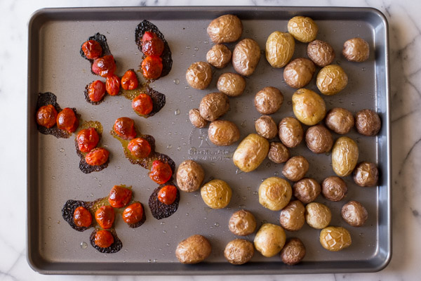 A baking sheet with the roasted tomatoes and potatoes.