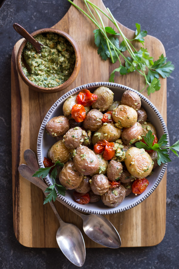 Roasted Baby Potatoes With Pesto in a serving bowl on a cutting board with a small wood bowl of Pesto, some fresh herbs and two spoons.