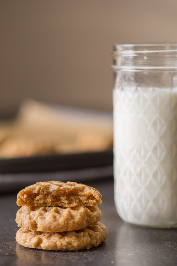 A half of a Small Batch Peanut Butter Cookie sitting on top of two whole cookies, with a glass of milk next to them.