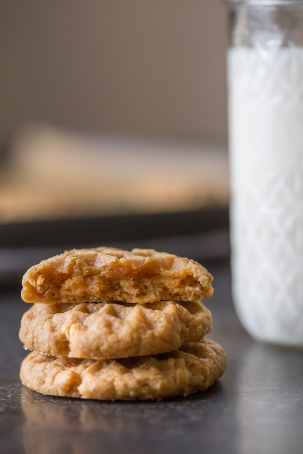 A half of a Small Batch Peanut Butter Cookie sitting on top of two whole cookies, and a glass of milk in the background.