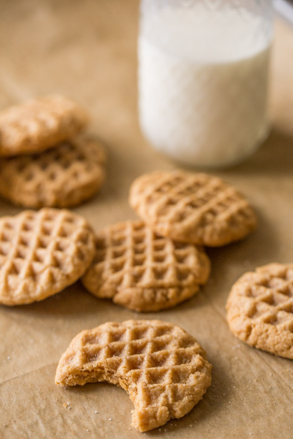 Small Batch Peanut Butter Cookies with a bite taken out of one of the cookies and a glass of milk in the background.
