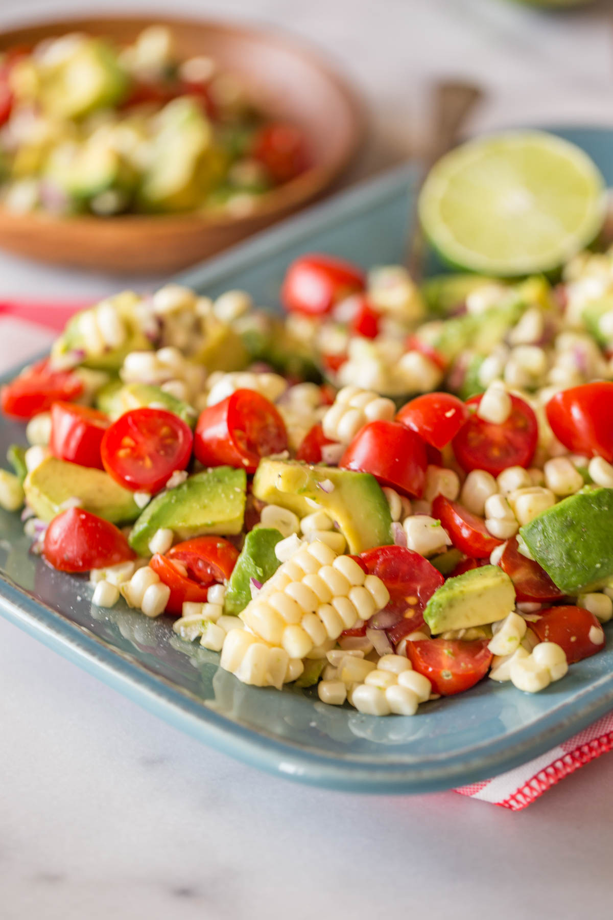 Corn, Tomato, and Avocado Salad on a platter, and a wood plate with a serving of the salad on it in the background.