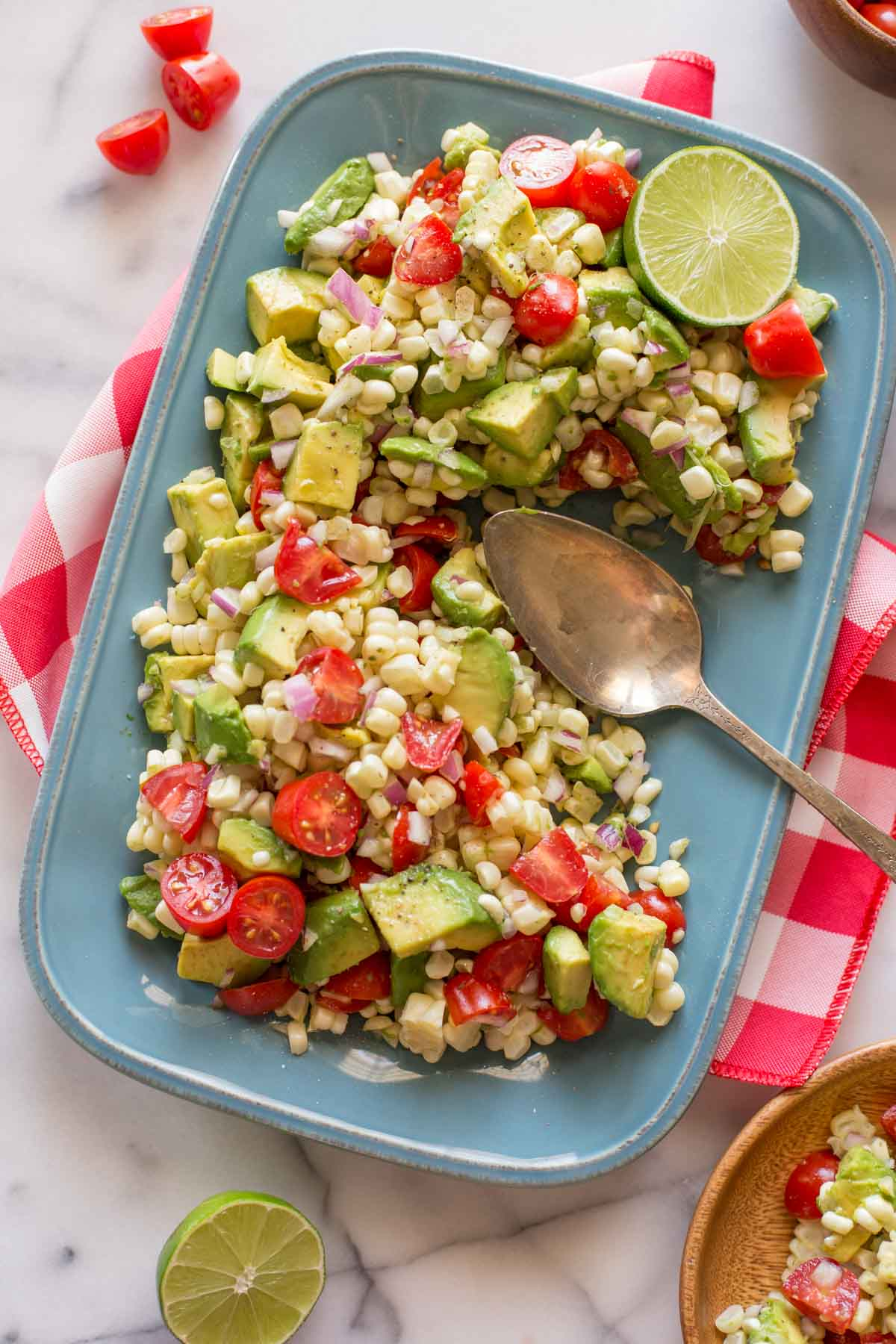 Corn, Tomato, and Avocado Salad on a platter with a serving spoon.