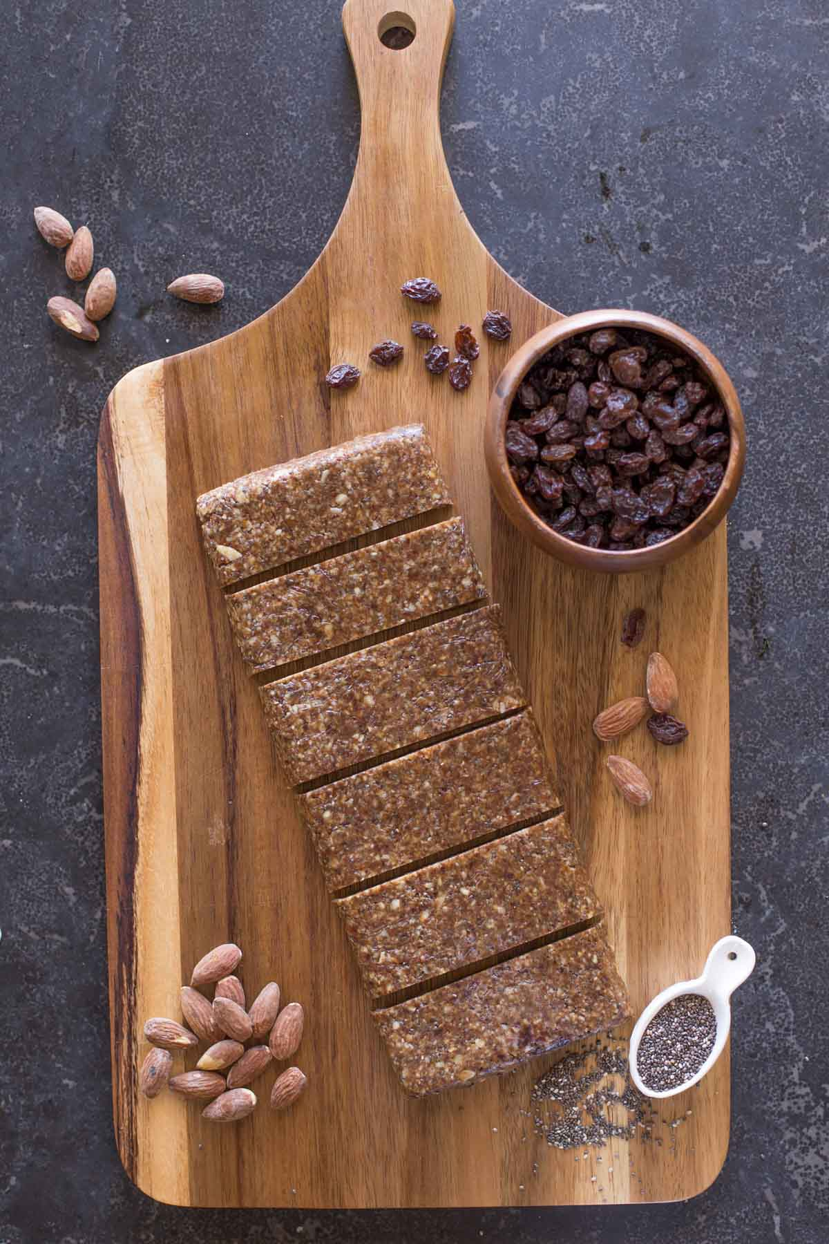 Five Ingredient No Bake Energy Bars on a cutting board, along with almonds, a small bowl of raisins and a spoon full of chia seeds.