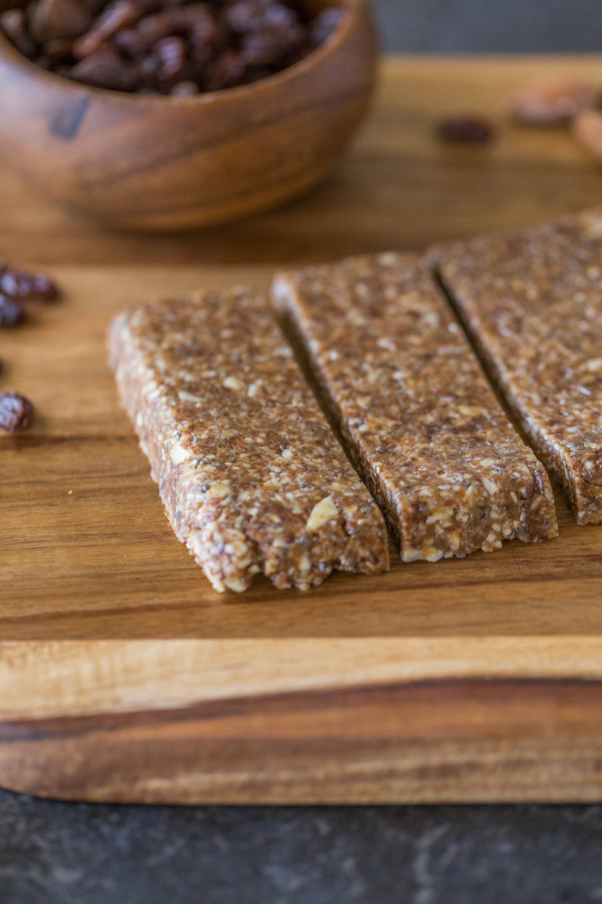 Five Ingredient No Bake Energy Bars on a cutting board, along with a small wood bowl of raisins.