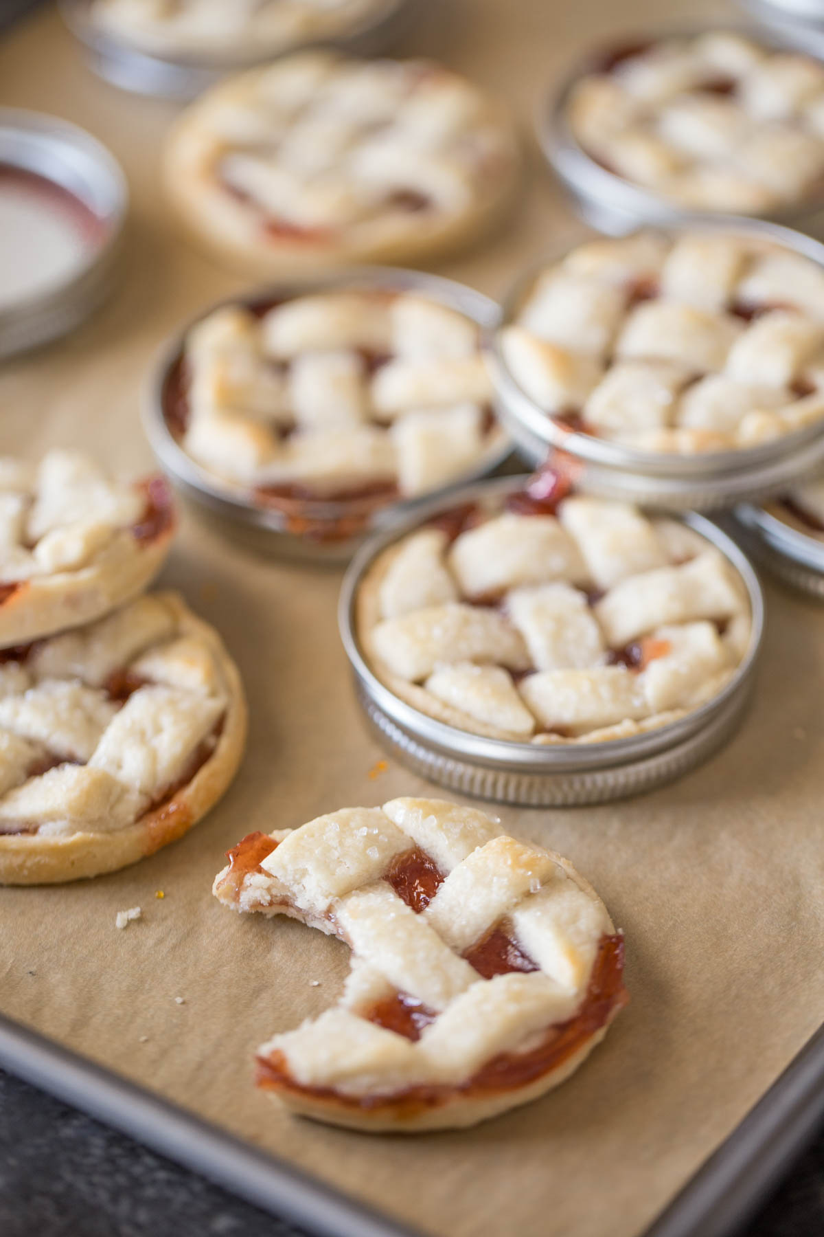 Mini Mason Jar Strawberry Pies on a parchment paper lined baking sheet after they have been baked, with some of the pies out of the lids and one pie with a bite taken out of it.