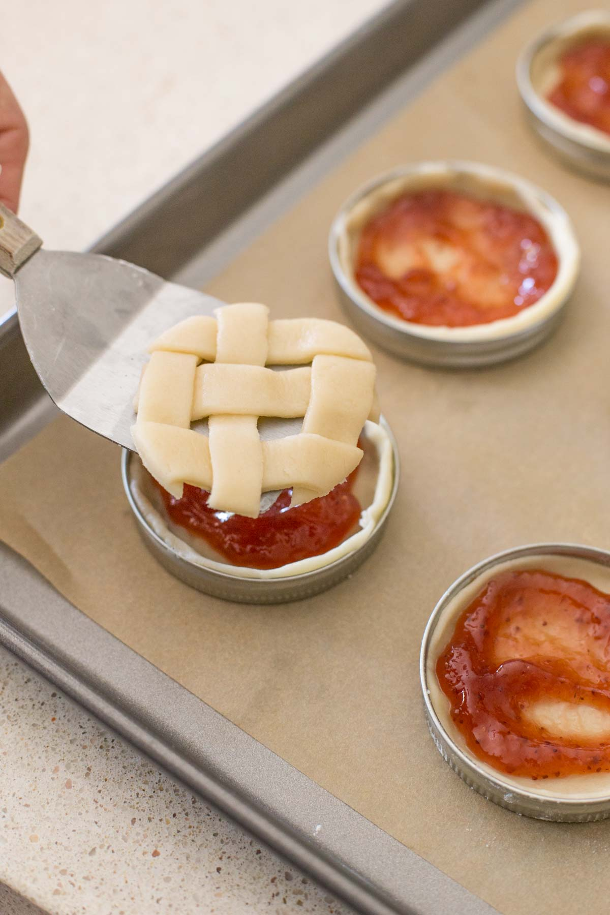 Mason jar lids arranged on a parchment paper lined baking sheet, with the pie dough and strawberry filling in them, and a metal spatula being used to transfer the circle lattice top onto the top of the pie.