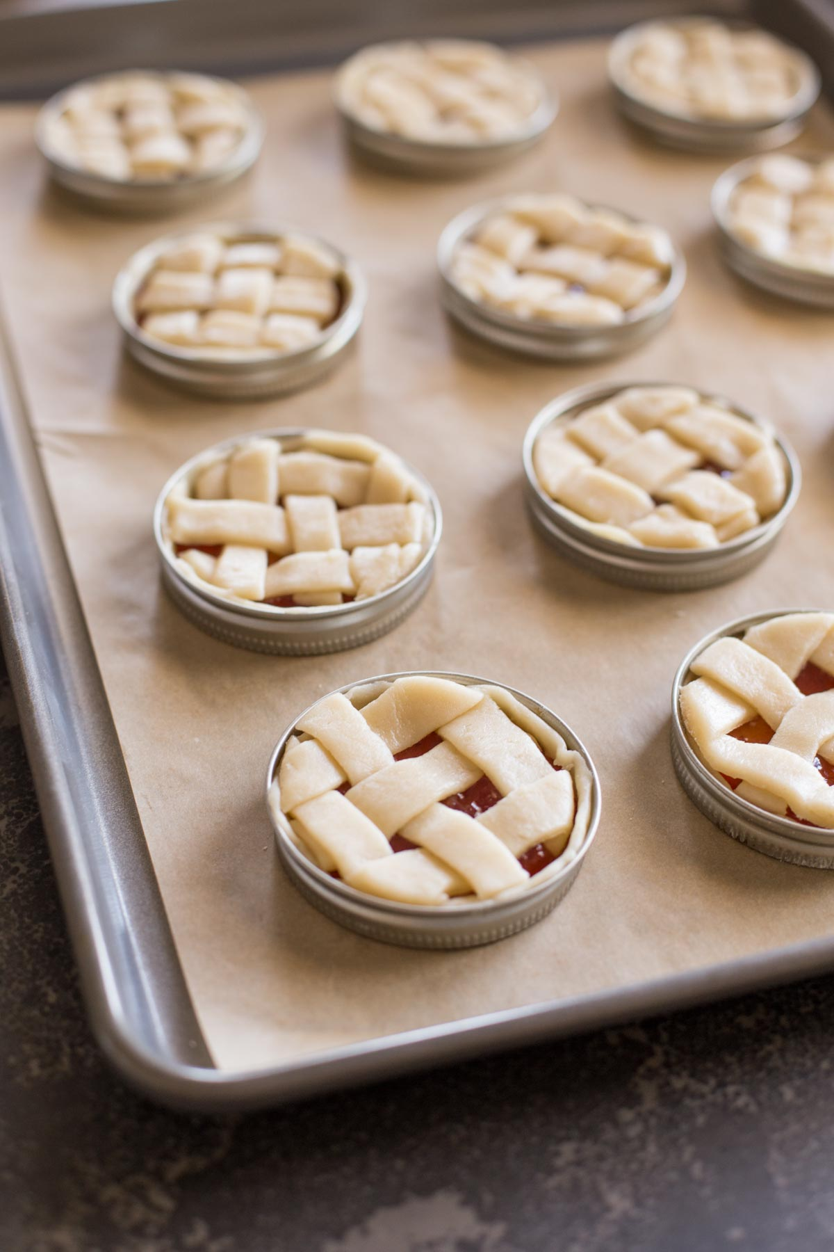 Mini Mason Jar Lid Strawberry Pies assembled and arranged on a parchment paper lined baking sheet before baking.