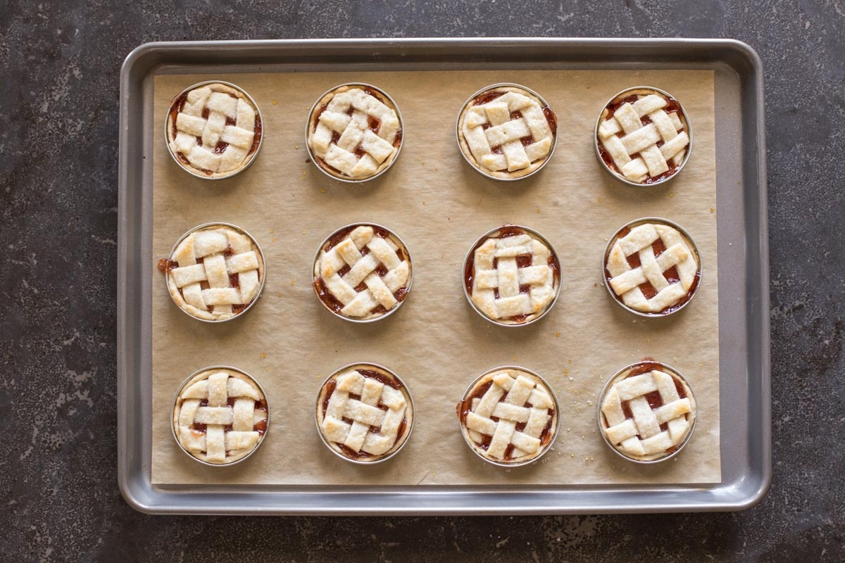 Mini Mason Jar Strawberry Pies on a parchment paper lined baking sheet after they have been baked.