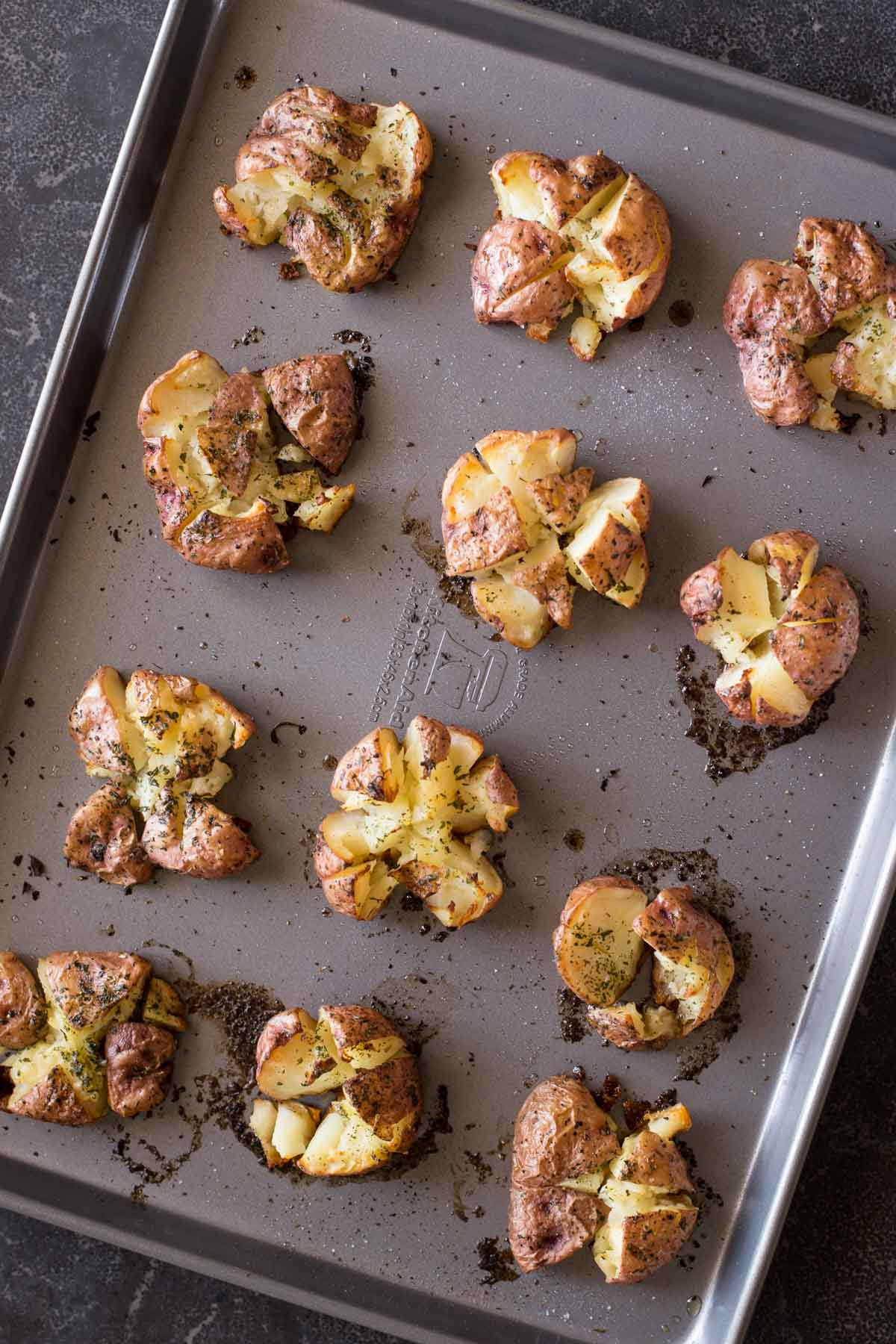 Smashed and Roasted Parmesan Potatoes on a baking sheet.