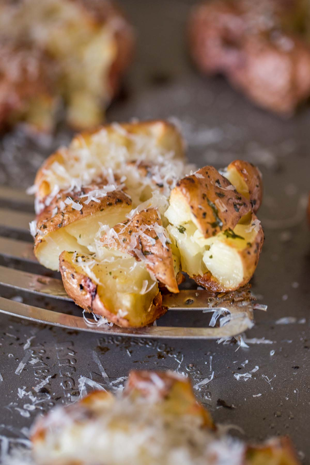 A spatula under a Smashed and Roasted Parmesan Potato on the baking sheet.