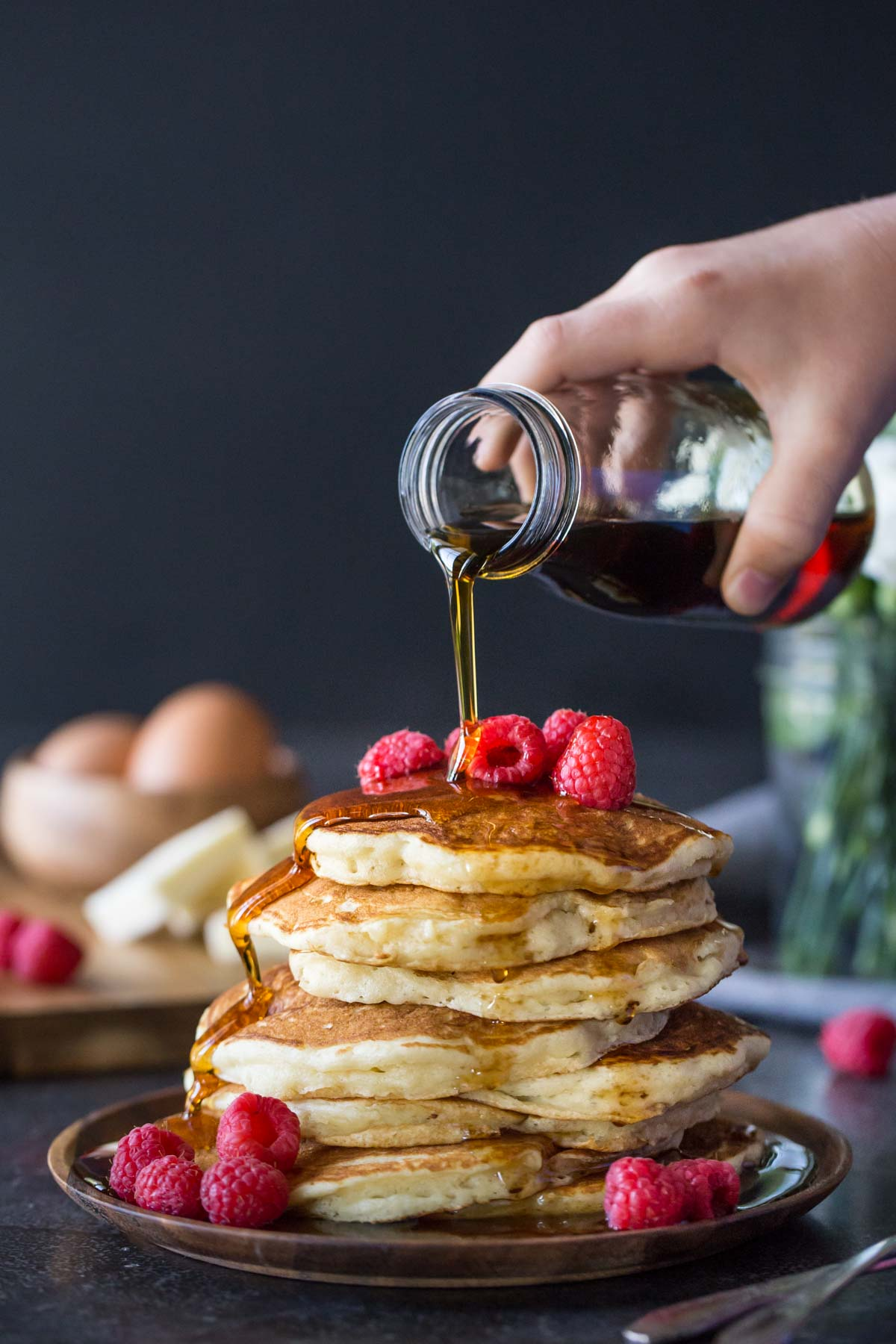 A stack of the Best Ever Buttermilk Pancakes on a plate, topped with fresh raspberries, with maple syrup being poured over them.