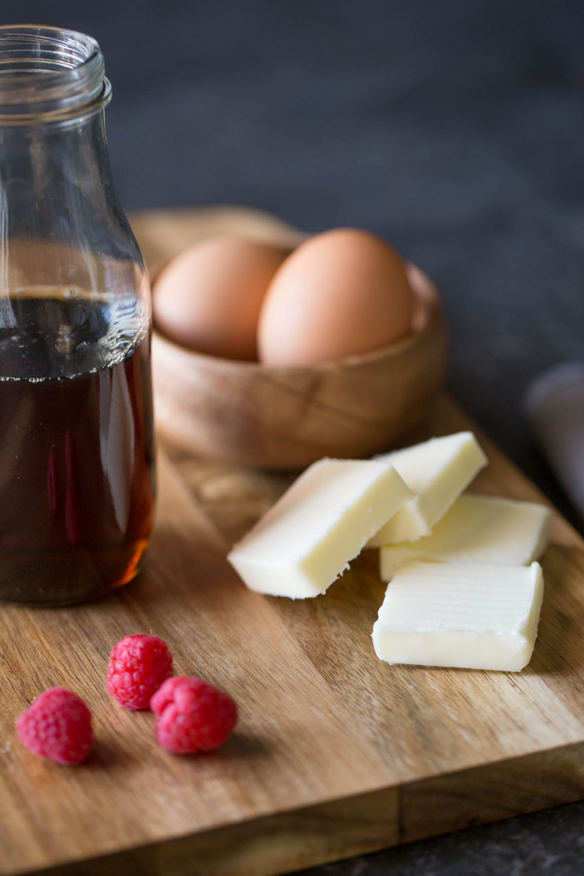 A cutting board with four pads of butter, a small wood bowl of brown eggs, a glass jar of maple syrup and a few fresh raspberries.