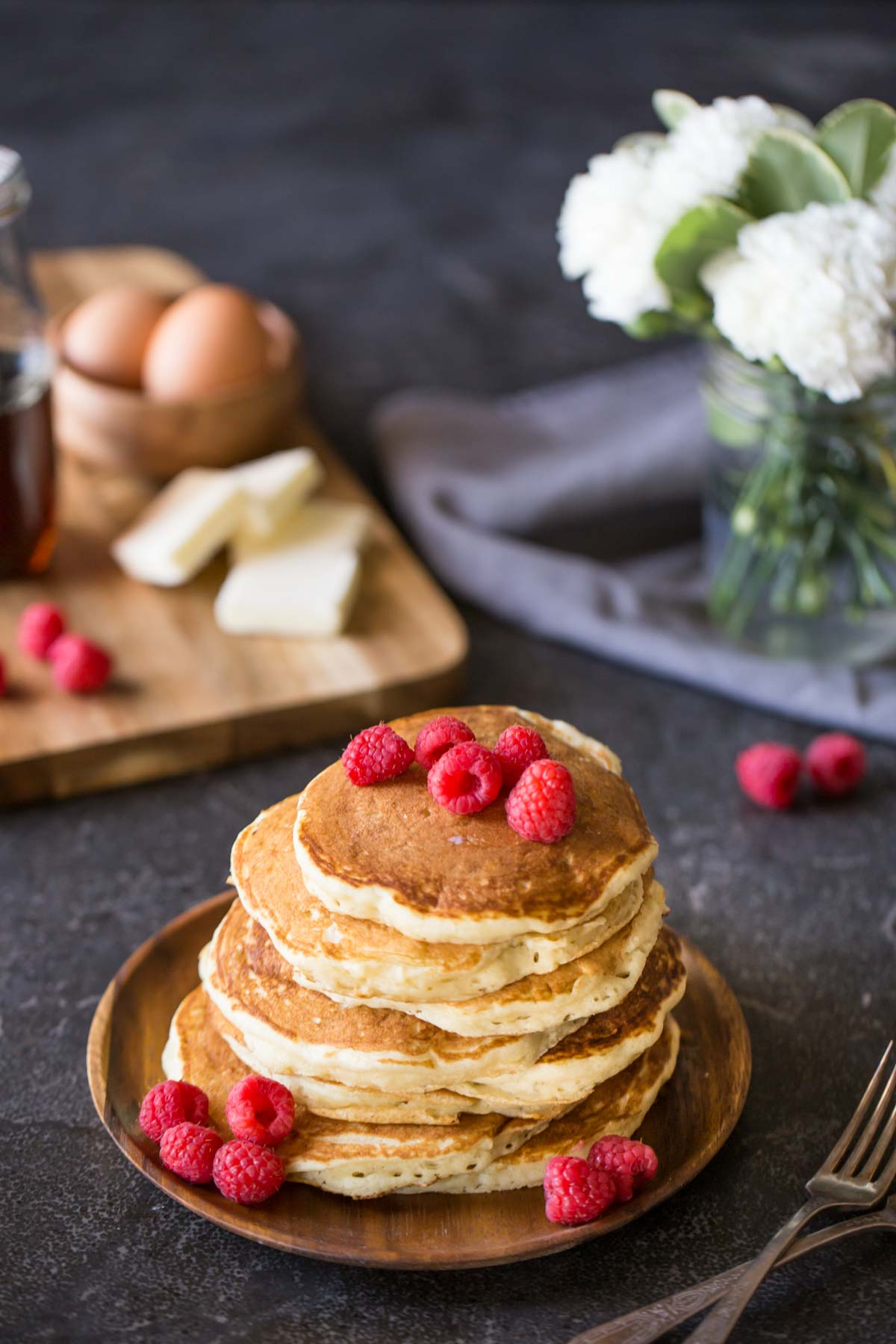 A stack of the Best Ever Buttermilk Pancakes on a plate, topped with fresh raspberries, with a cutting board with four pads of butter, a small wood bowl of brown eggs, a glass jar of maple syrup and a few fresh raspberries in the background, along with a flower arrangement.