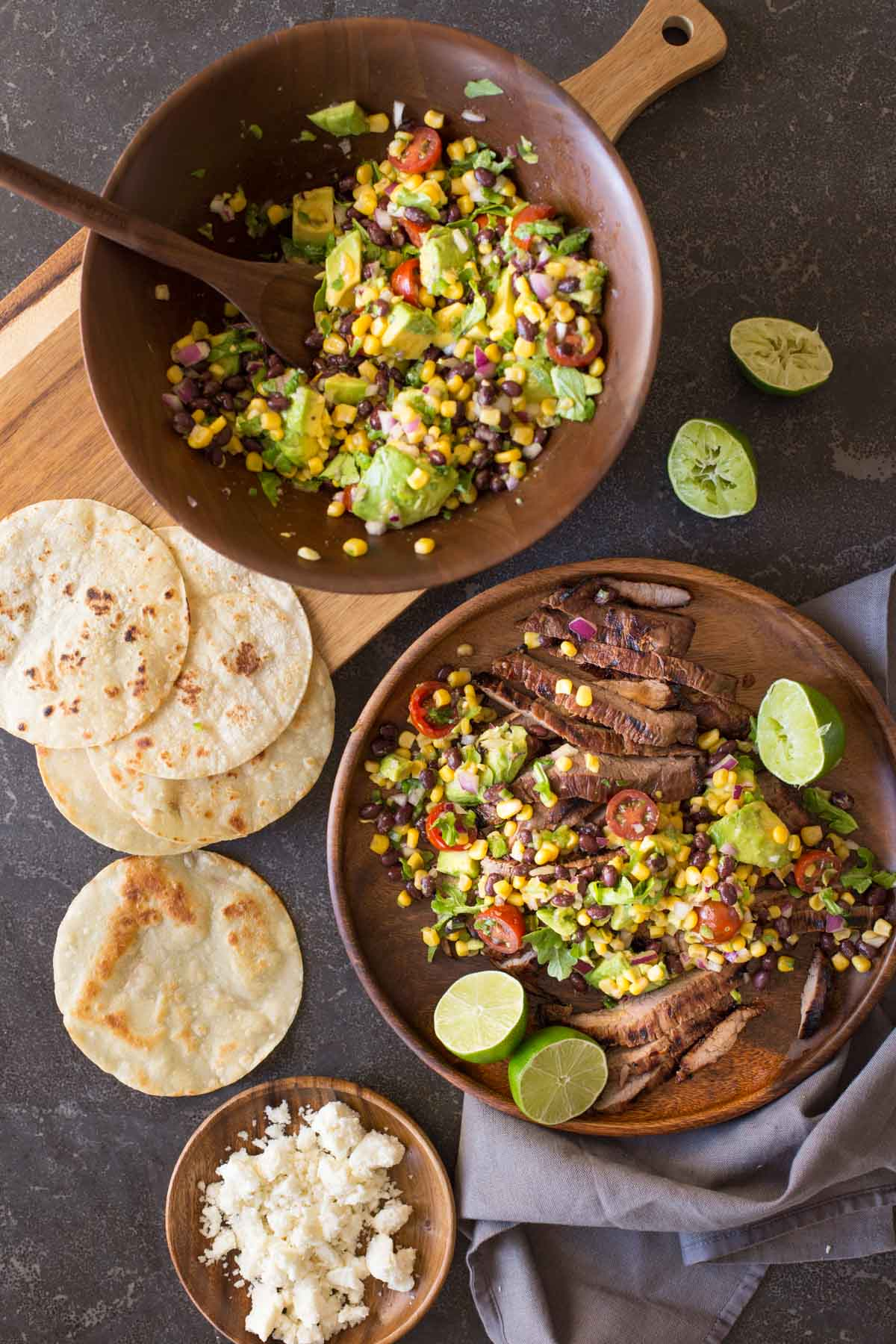 A large wood plate of sliced grilled marinated flank steak and avocado salad with limes cut in half, sitting next to a large wood bowl of avocado salad, some small taco tortillas and a small wood plate of crumbled queso fresco.