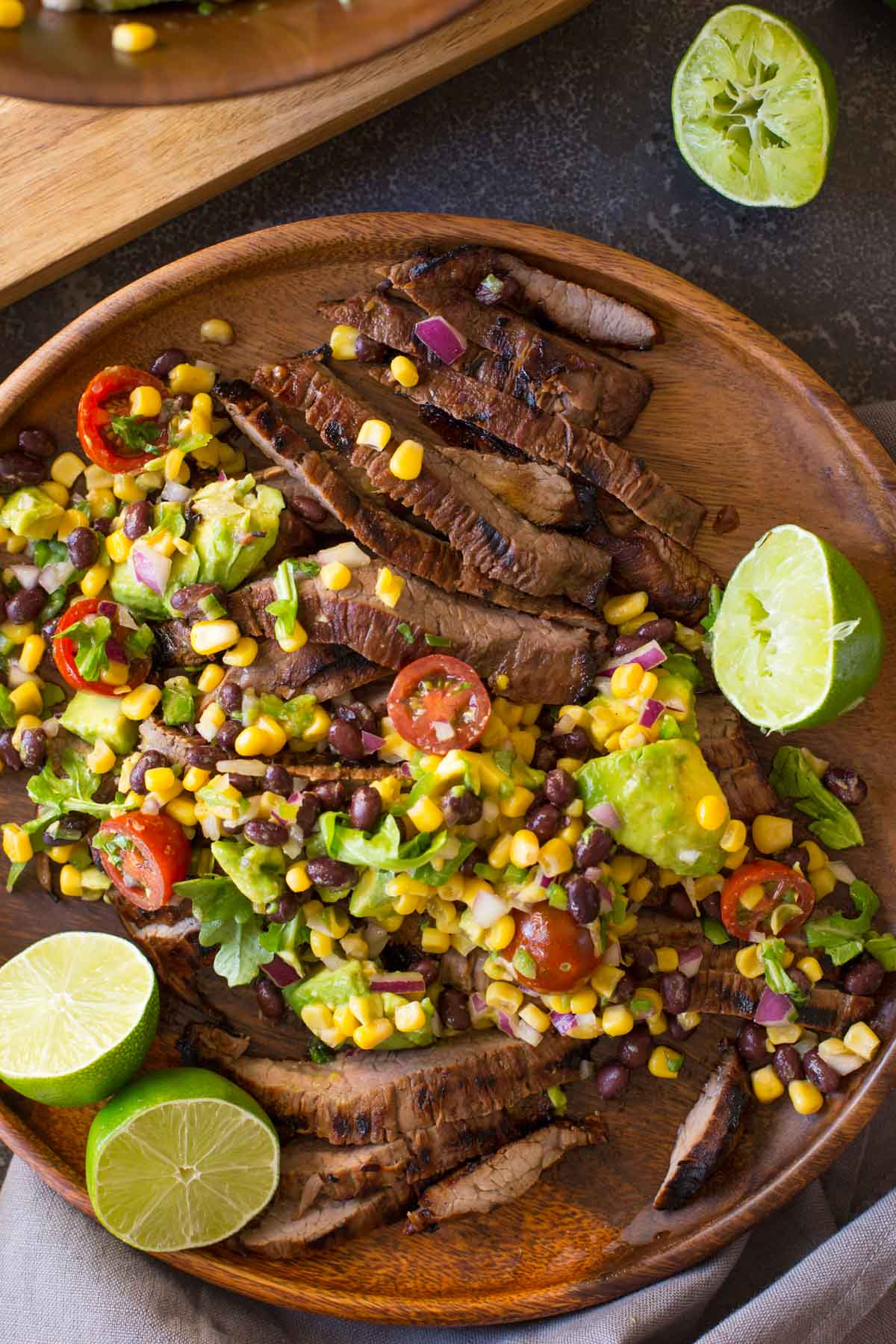 A large wood plate of sliced grilled marinated flank steak and avocado salad with limes cut in half.