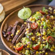 Grilled, marinated flank steak sliced thinly, wrapped in a warm corn tortilla and topped with a fresh mixture of avocado, tomato, corn, and black beans!