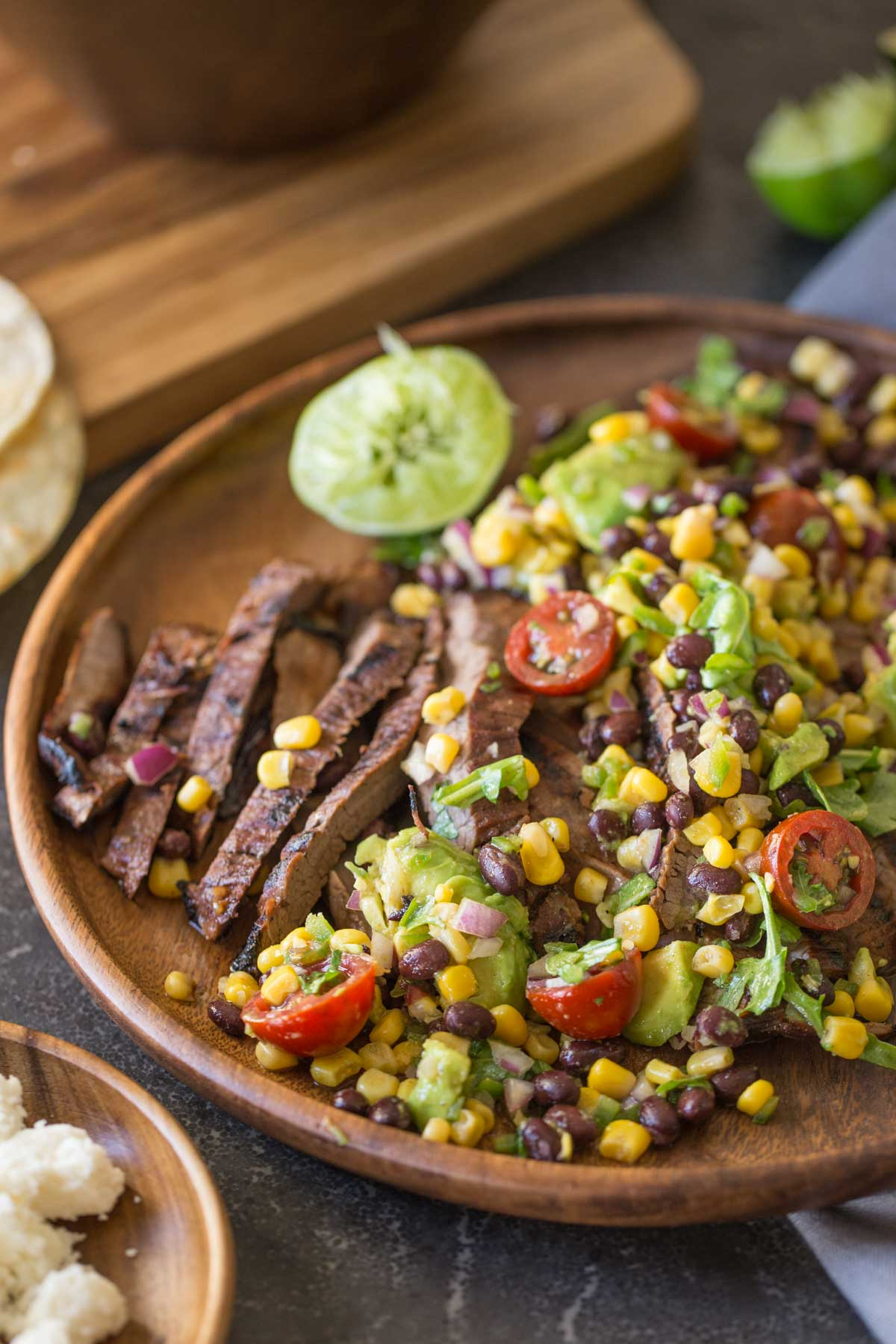 A large wood plate of sliced grilled marinated flank steak and avocado salad.