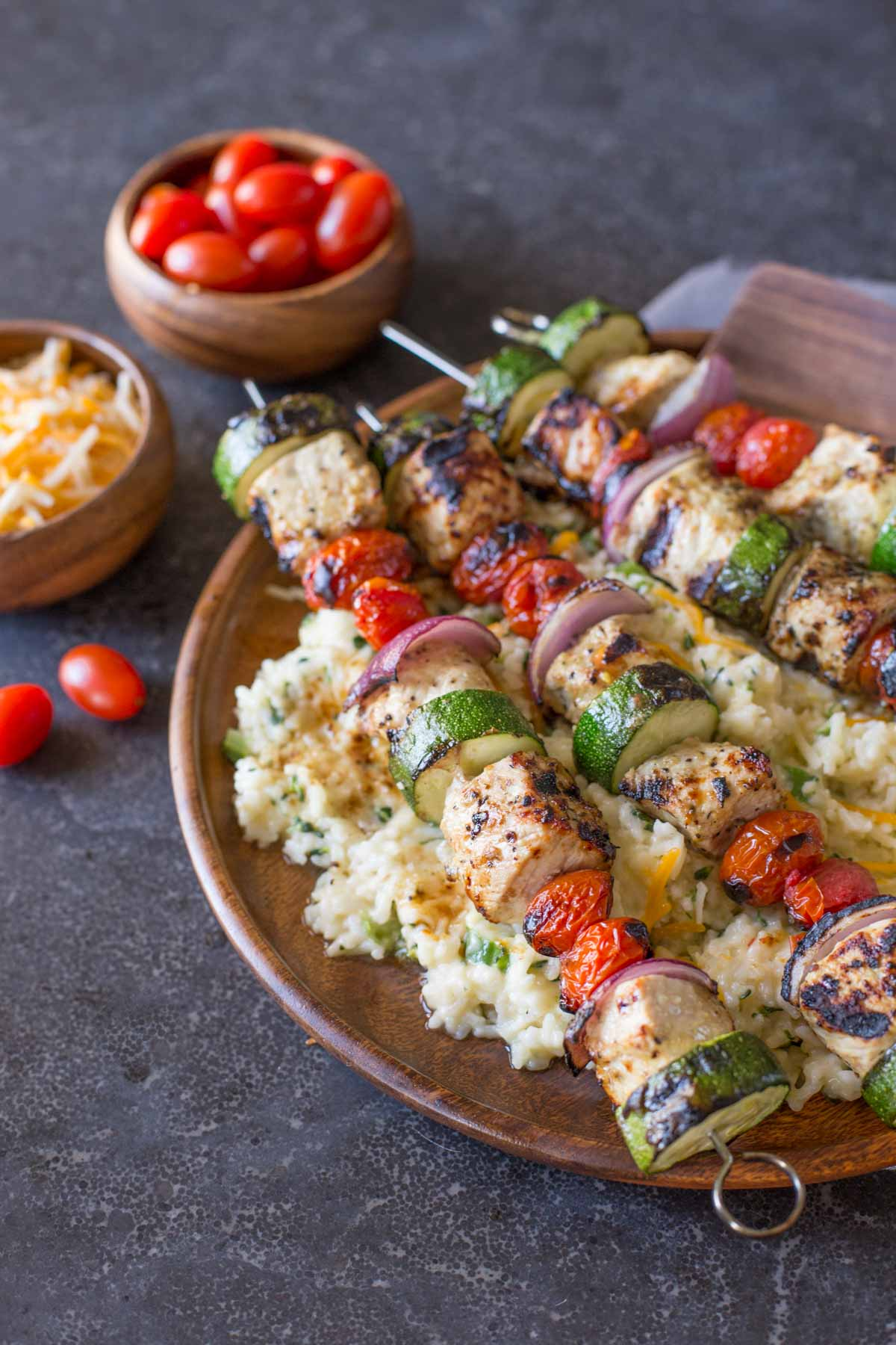 Pork Tenderloin Kabobs served over Cheesy Broccoli Rice on a large wood plate, with a small wood bowl of shredded cheese and a small wood bowl of grape tomatoes in the background.