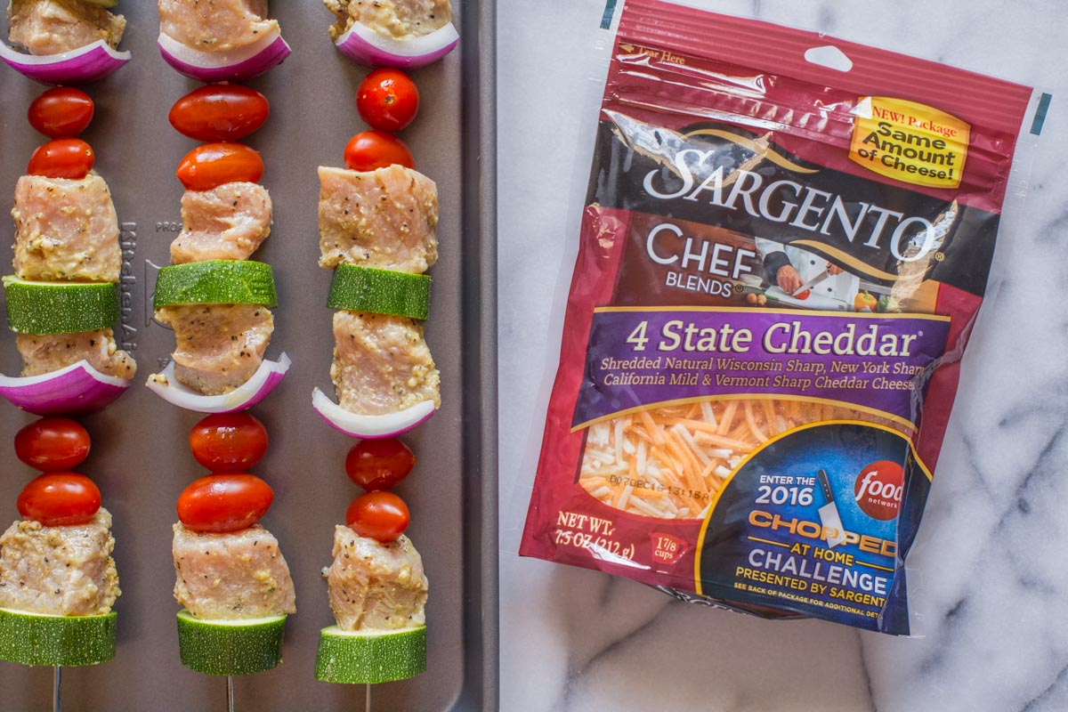 Pork Tenderloin Kabobs on a baking sheet before being grilled, with a package of Sargento® Chef Blends 4 State Cheddar next to the baking sheet.