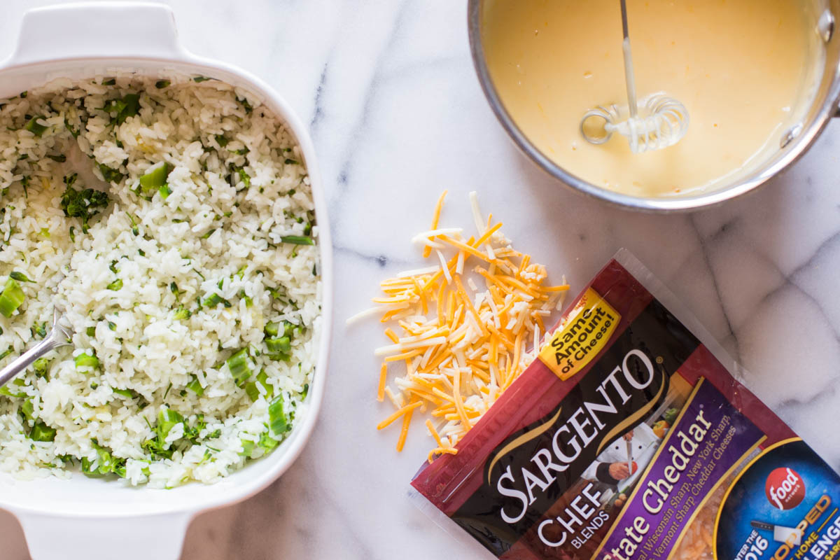 A baking dish with white rice and broccoli, sitting next to a package of Sargento® Chef Blends 4 State Cheddar and a bowl of the creamy cheddar cheese sauce for the Cheesy Broccoli Rice.