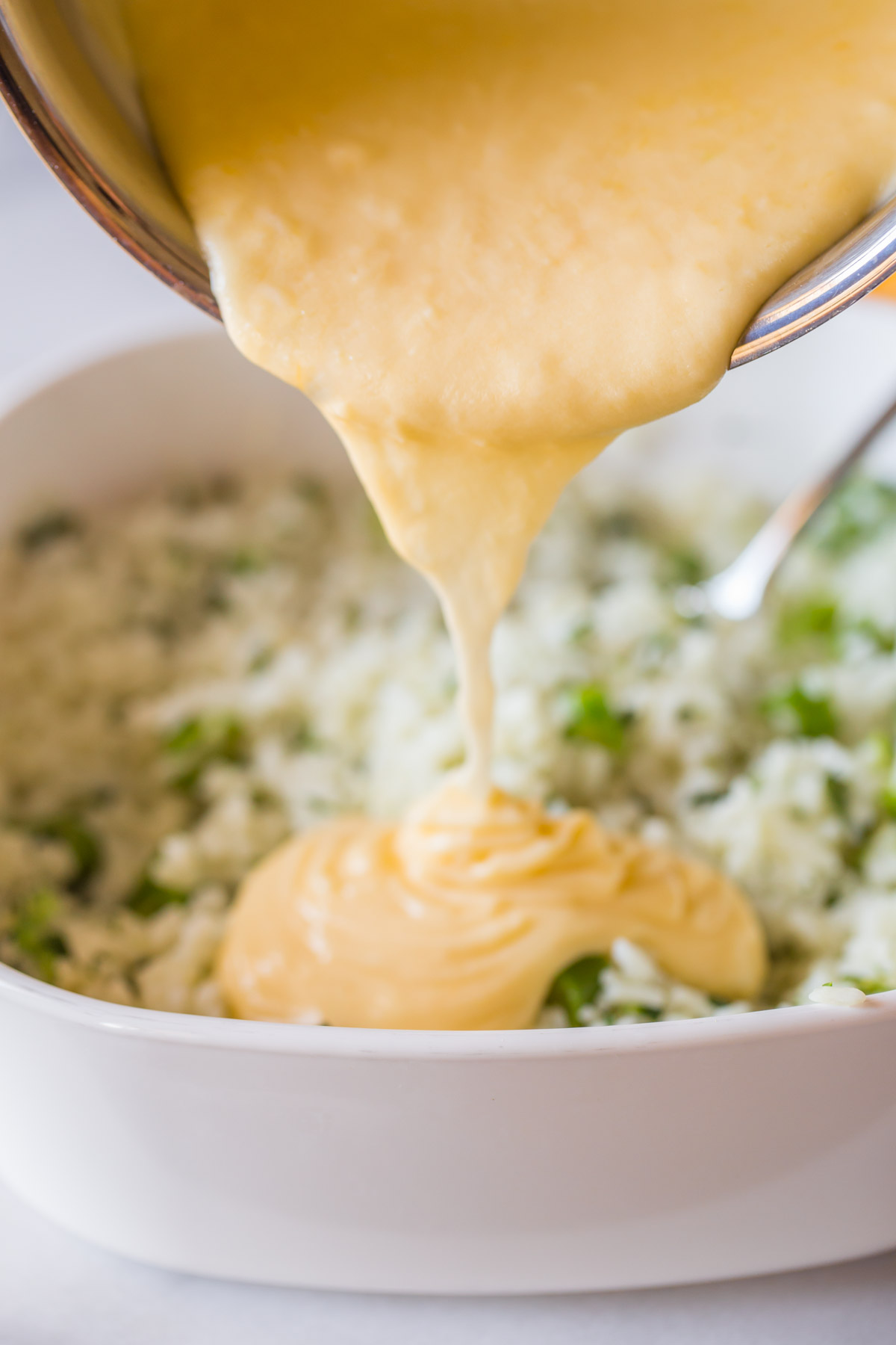 The creamy cheddar cheese sauce being poured on top of the baking dish of white rice and broccoli for the Cheesy Broccoli Rice.