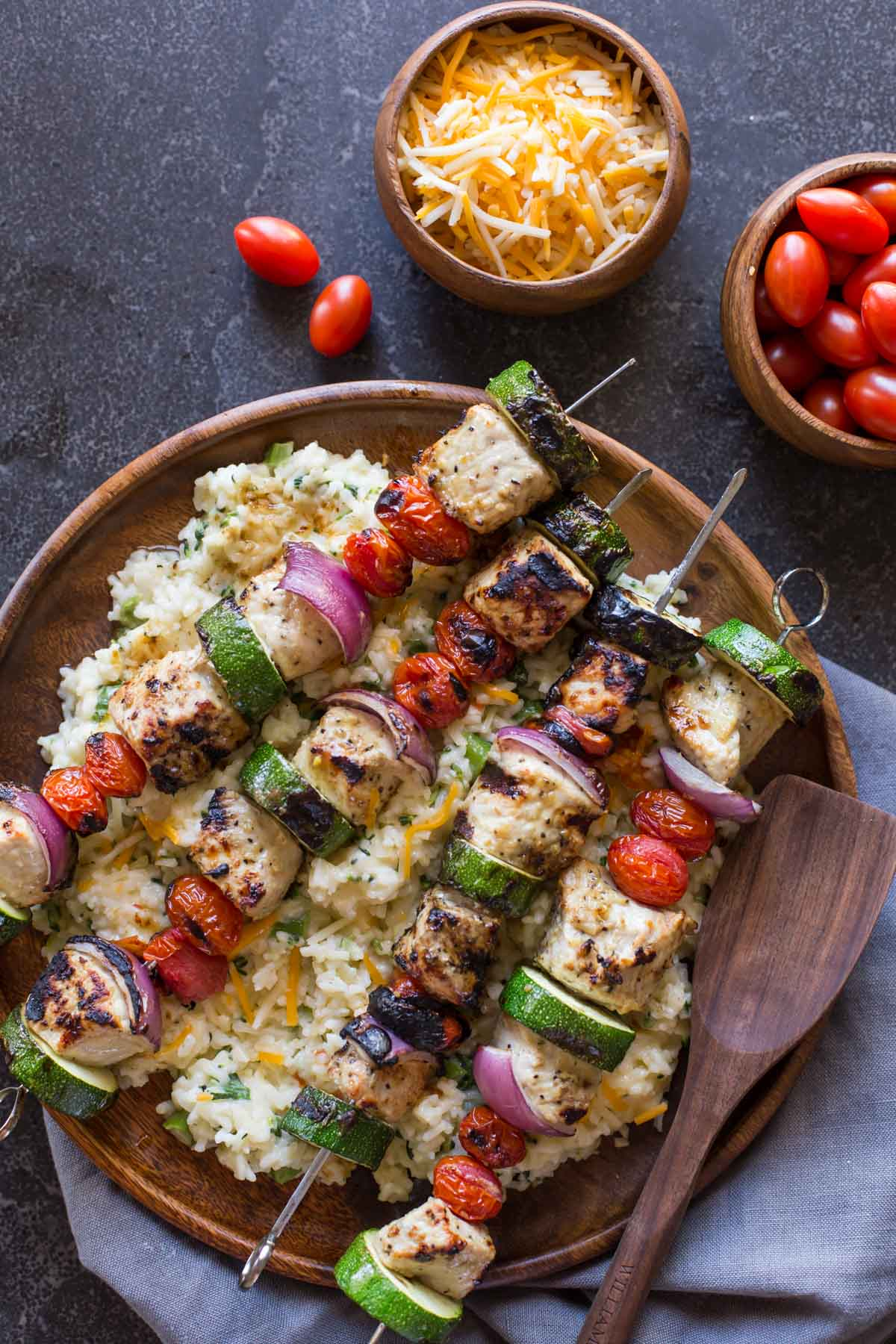 Pork Tenderloin Kabobs served over Cheesy Broccoli Rice on a large wood plate, with a small wood bowl of shredded cheese and a small wood bowl of grape tomatoes next to it.