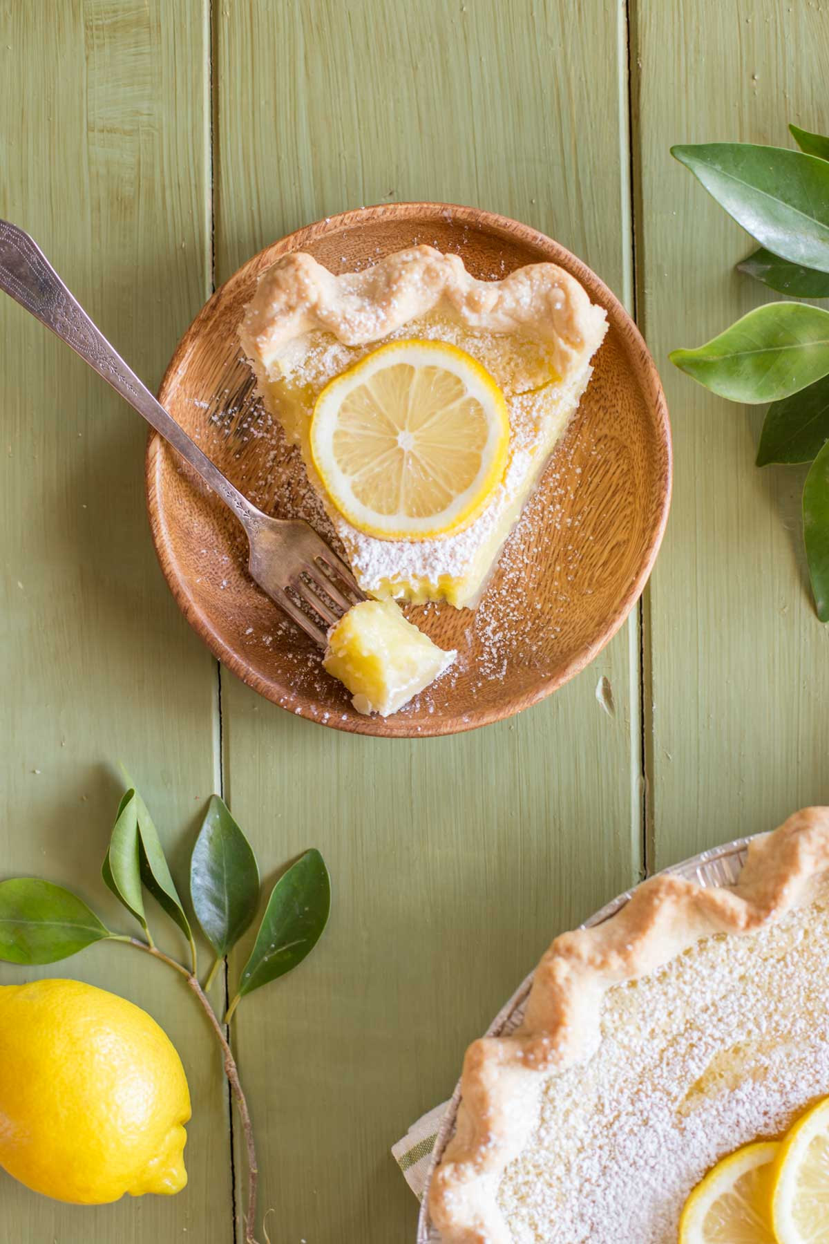 A slice of Whole Lemon Pie dusted with powdered sugar and topped with a lemon slice, on a plate with a fork with a piece of pie on it, siting next to the Whole Lemon Pie pan.