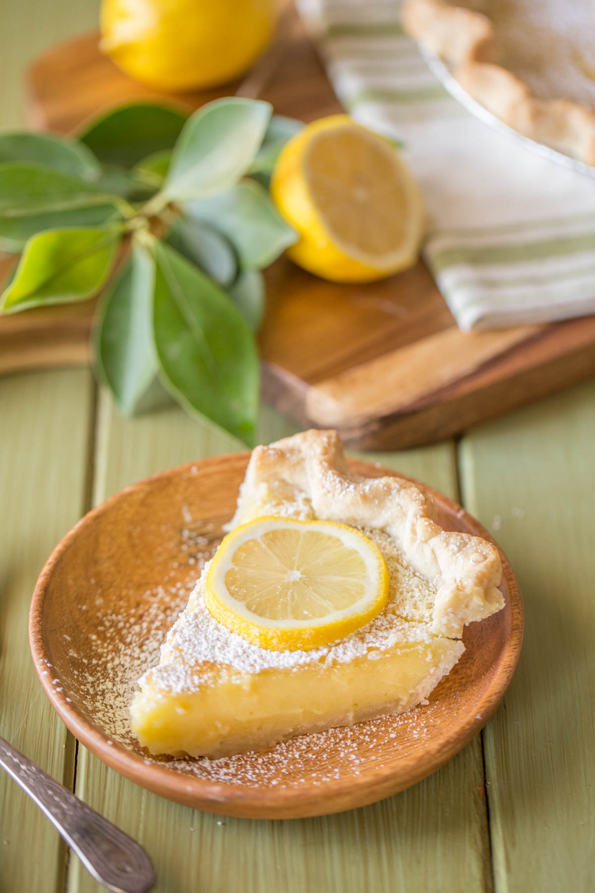 A slice of Whole Lemon Pie dusted with powdered sugar and topped with a lemon slice, on a plate.