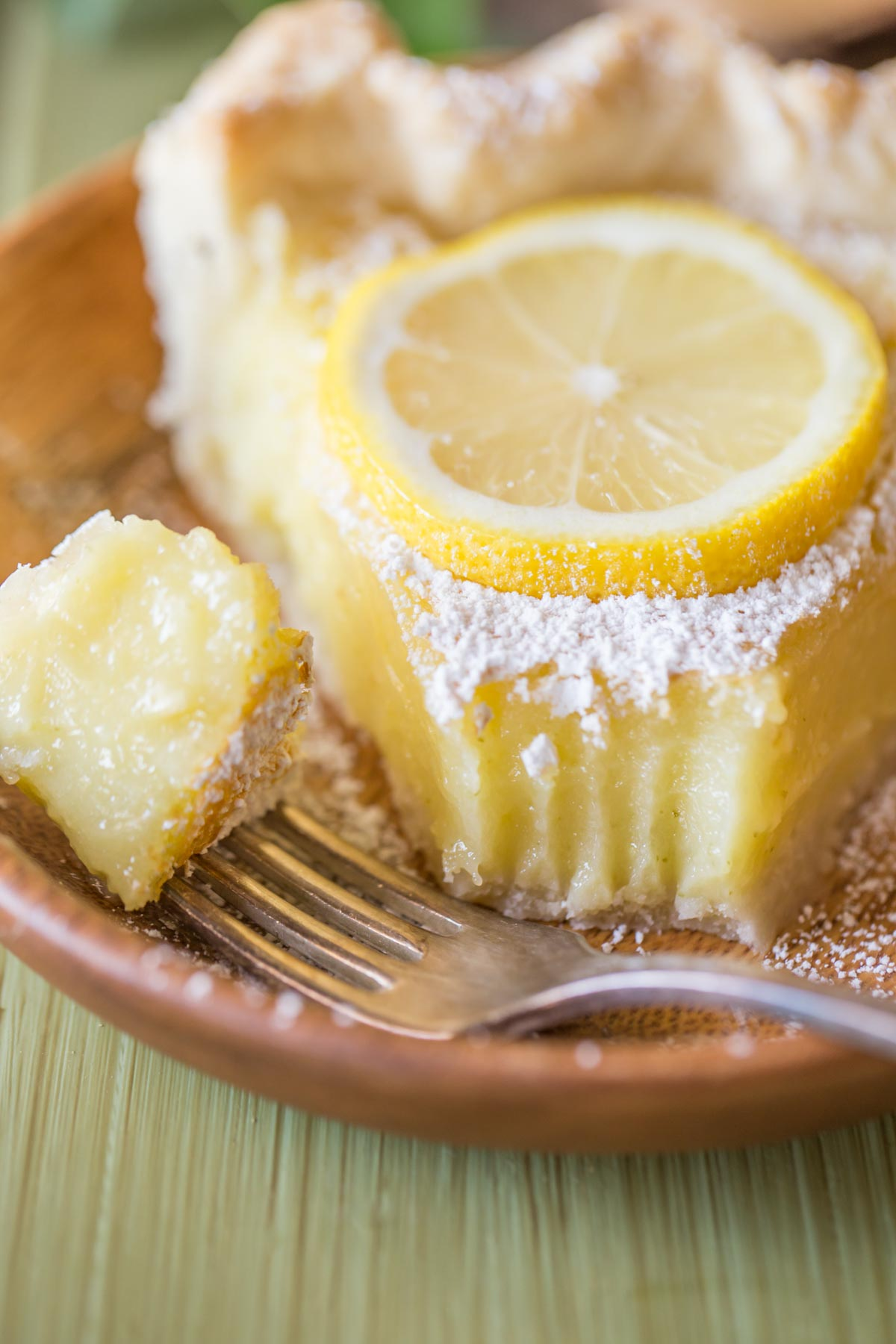 A slice of Whole Lemon Pie dusted with powdered sugar and topped with a lemon slice, on a plate with a fork with a piece of pie on it.