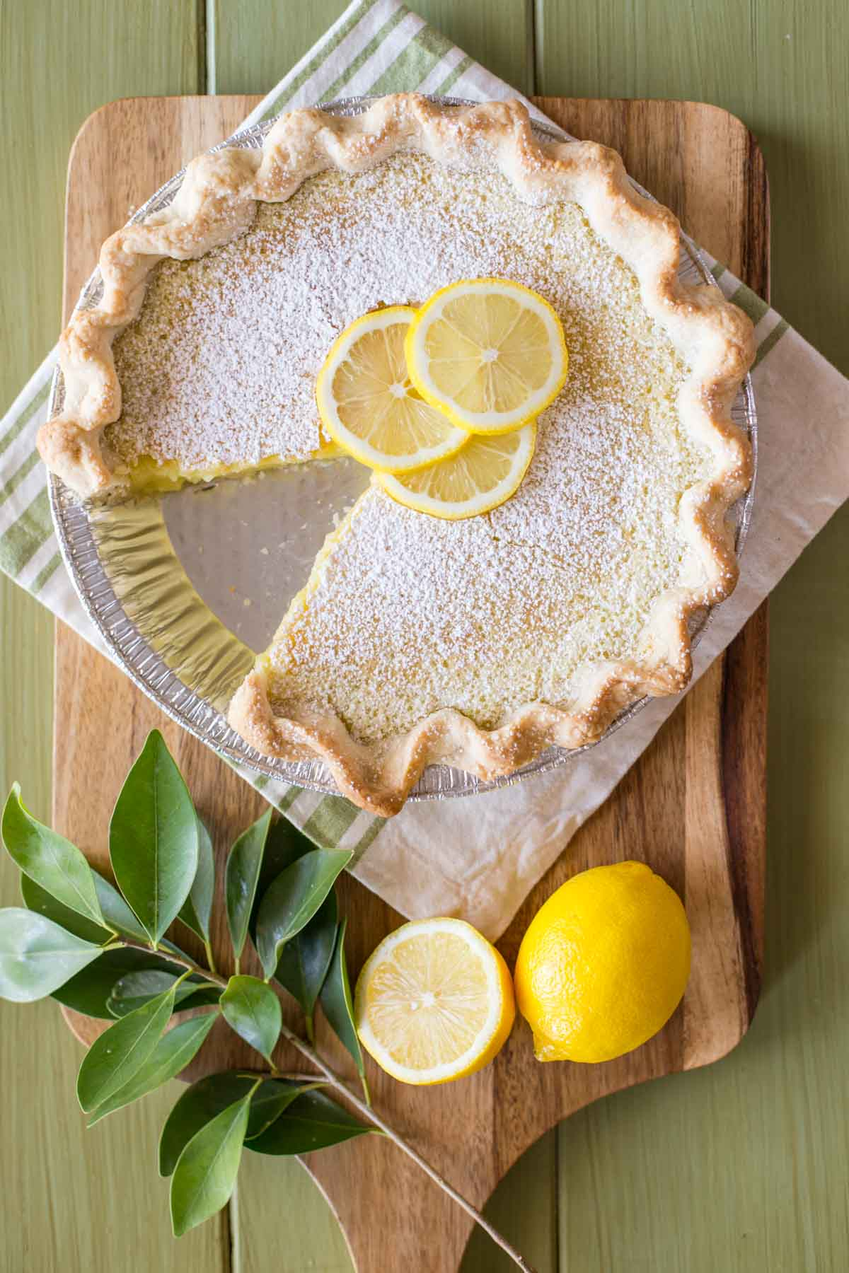 A Whole Lemon Pie dusted with powdered sugar and garnished with lemon slices, with one slice of pie missing, sitting on a cutting board with some lemons and tree leaves.