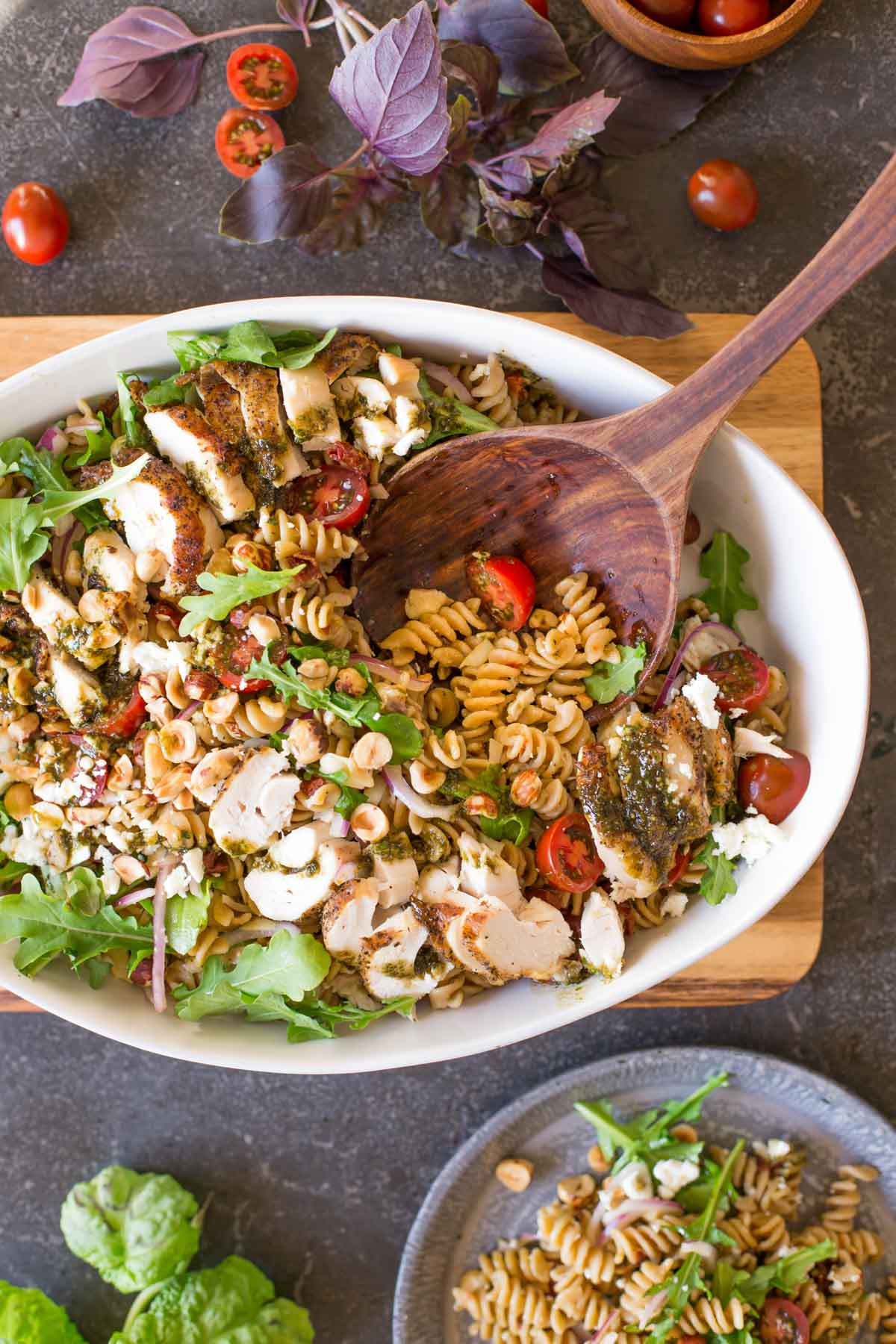 Whole Wheat Pasta Salad With Honey Basil Balsamic Vinaigrette in a large serving bowl with a wooden spoon in it, and a serving of the pasta salad on a plate next to it.