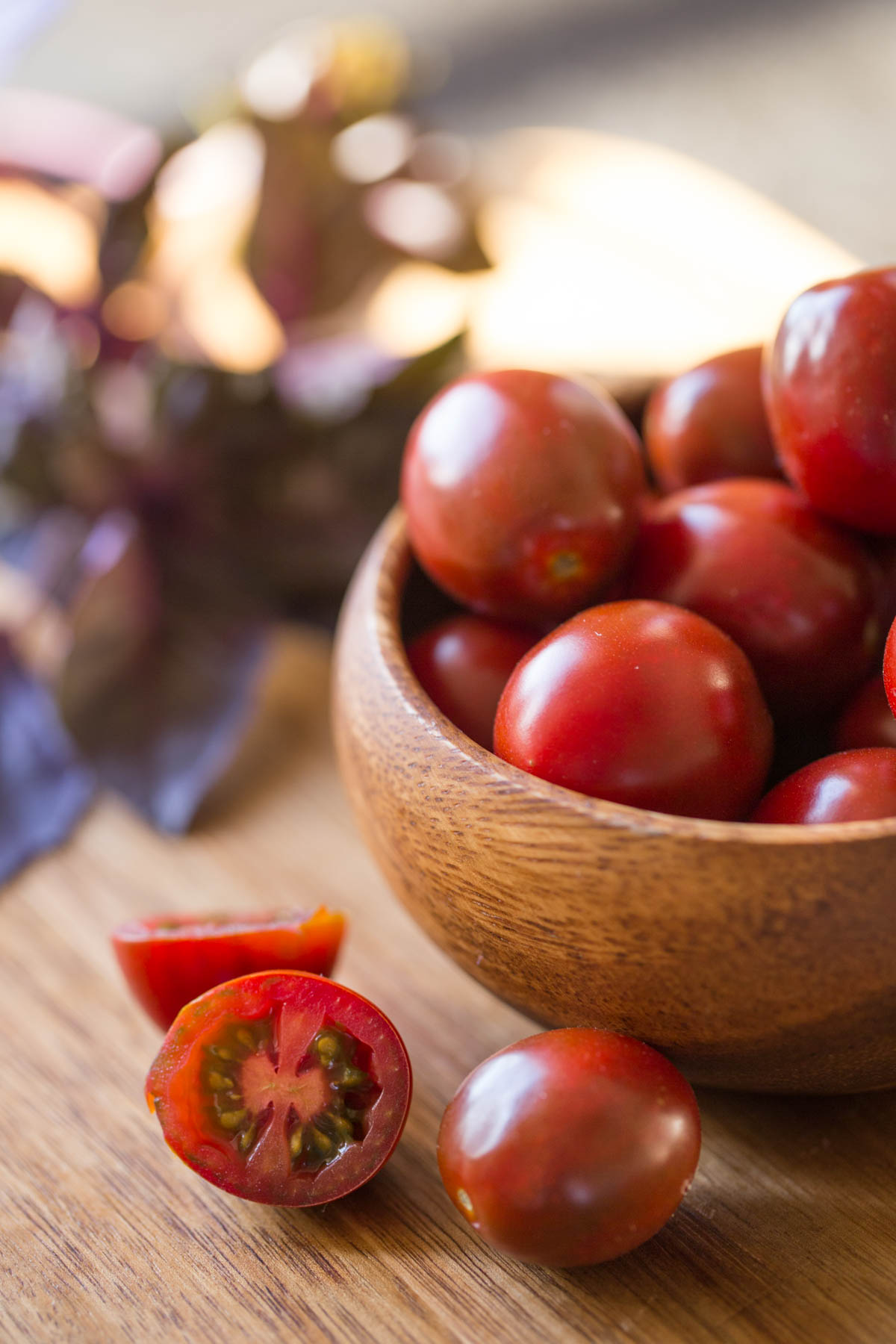 A small wood bowl of grape tomatoes, with a few tomatoes sitting next to the bowl.