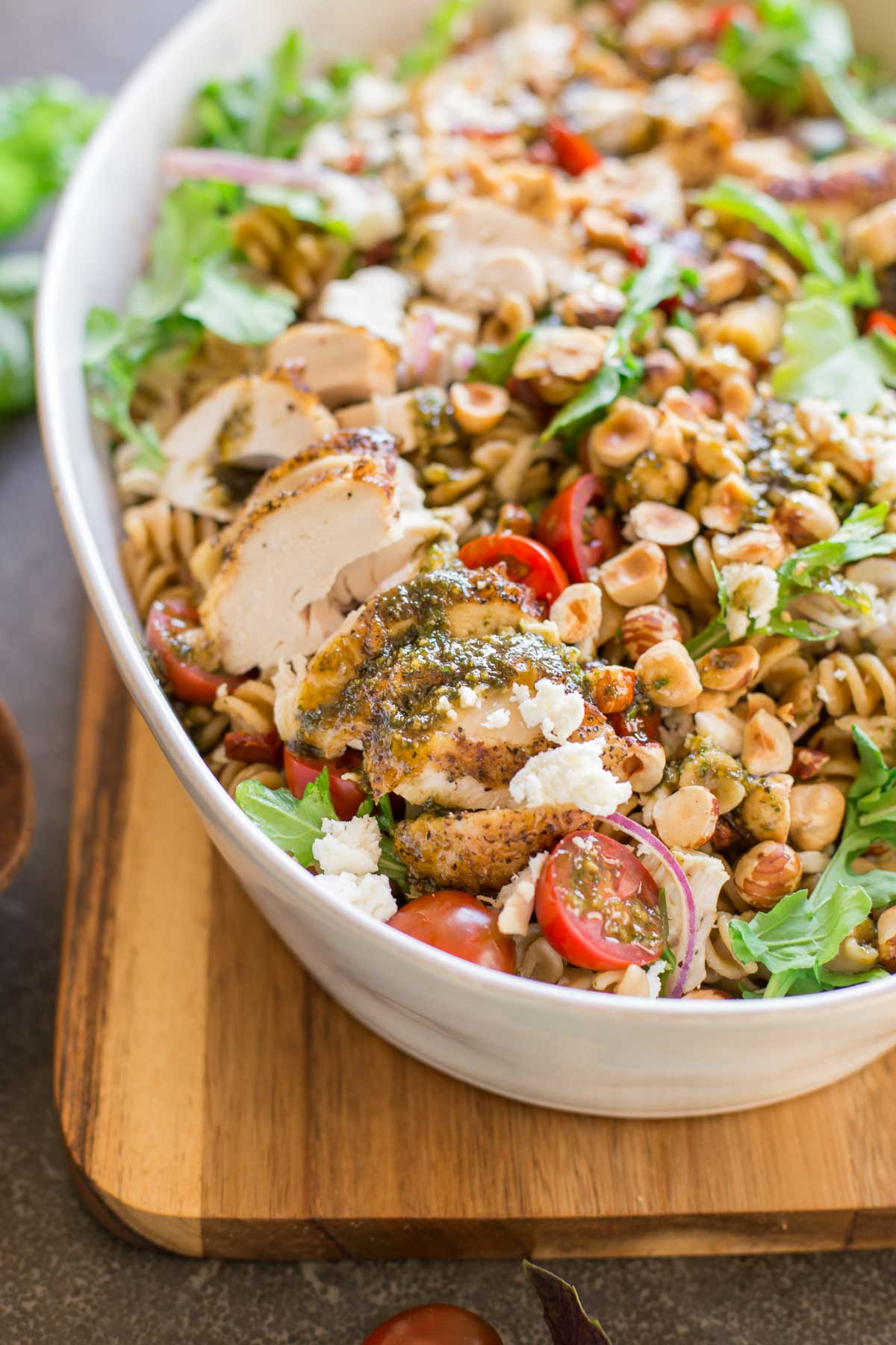 Whole Wheat Pasta Salad With Honey Basil Balsamic Vinaigrette in a large serving bowl, sitting on a cutting board.