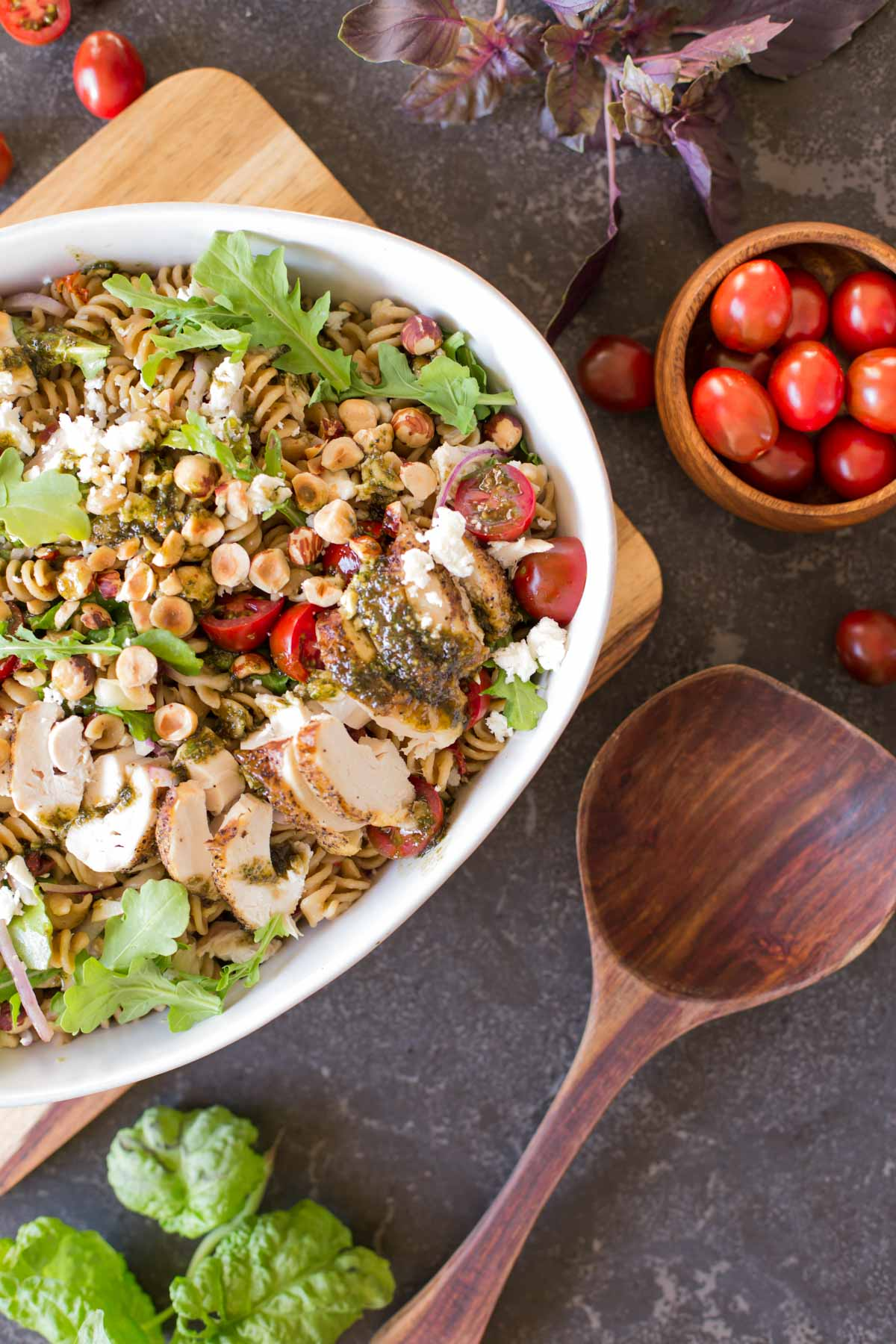 Whole Wheat Pasta Salad With Honey Basil Balsamic Vinaigrette in a large serving bowl with a wooden spoon next to it, as well as a small wood bowl of grape tomatoes.
