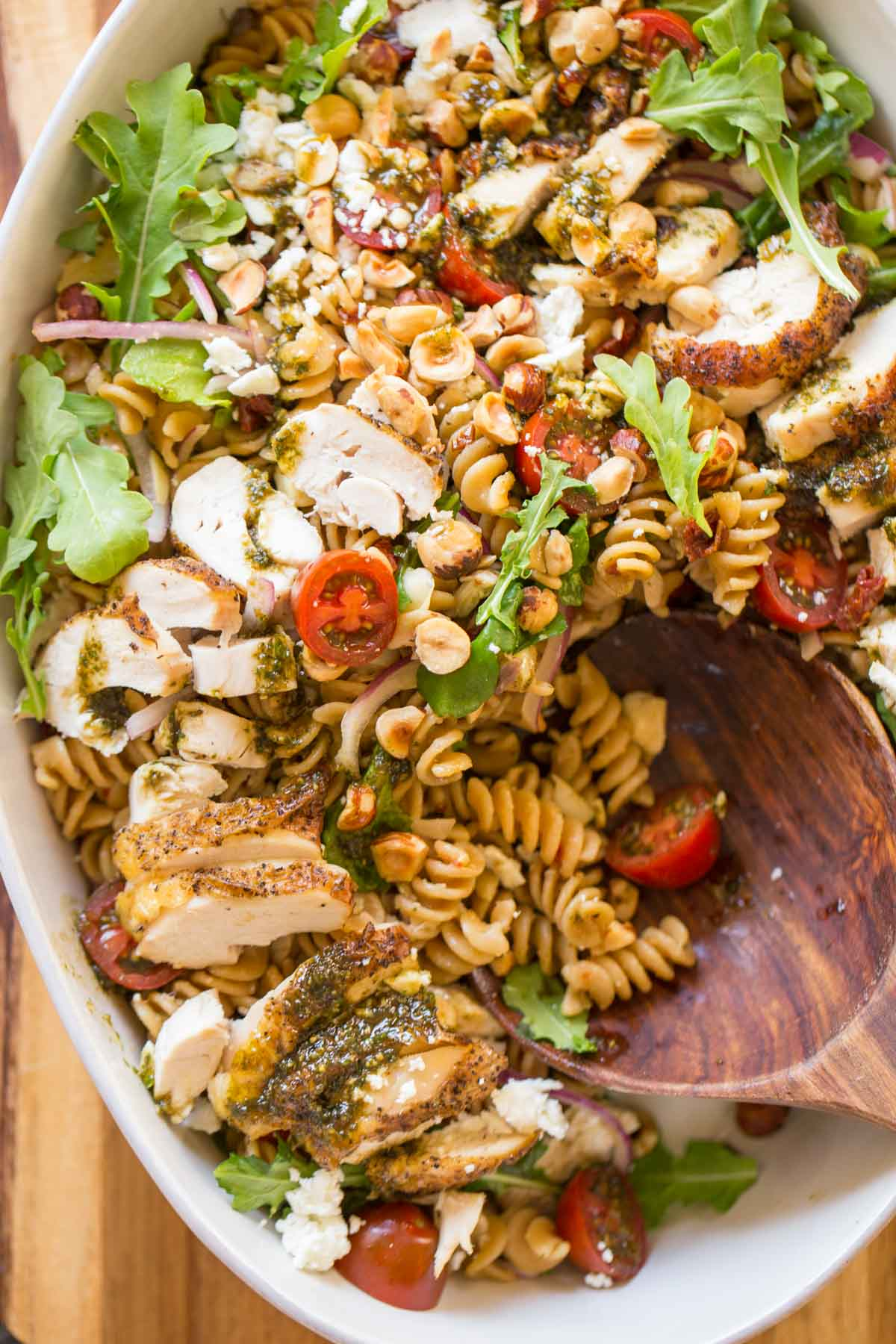 Whole Wheat Pasta Salad With Honey Basil Balsamic Vinaigrette in a large serving bowl with a wooden spoon in it.