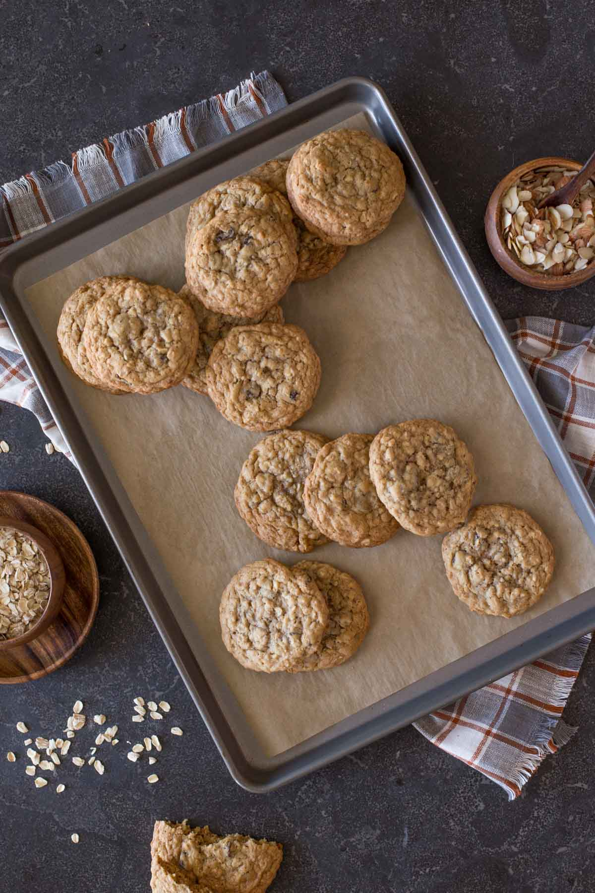Bakery Style Oatmeal Raisin Cookies on a parchment paper lined baking sheet, with a small wood bowl of oats on one side of the baking sheet, and a small wood bowl of slice almonds on the other side.